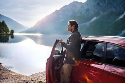 Man leaning against his Hyundai i30 N Line Wagon, looking out on a mountain lake