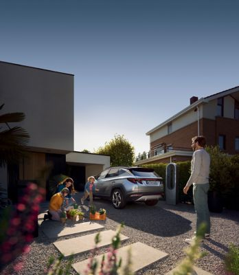 The all-new Hyundai TUCSON Plug-in Hybrid compact SUV parked in front of a house with children.